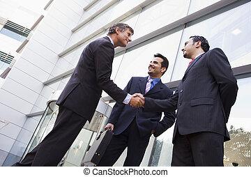 handlowy zaludniają, potrząsające ręki, zewnątrz, biuro
