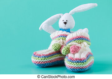 Handmade baby booties and rabbit toy