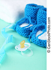Handmade baby booties with pacifier on mint background