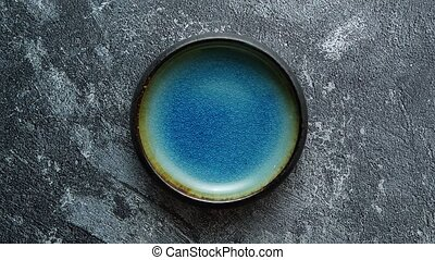 Handmade brown and blue glaze rustic pottery bowl placed on rusty background
