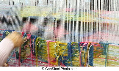 Handmade carpet embroidery. Women's hands create a pattern using multi-colored threads. Hammer for embroidery quors, stuffing threads. Close up view.
