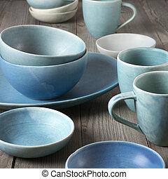 Rustic handmade blue ceramic dishware set on wooden table.