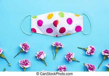Handmade colorful cloth mask with carnation flower on blue background.