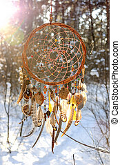 Handmade colorfull dream catcher in the snowy forest. Tribal...