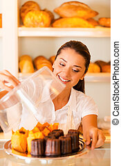Handmade cookies for sale. Beautiful young woman in apron carrying plate with fresh cookies and smiling while standing in bakery shop