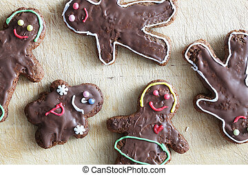 Handmade decorated gingerbread people lying on wooden table.