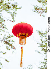 Handmade Fabric red lanterns isolated on the green leaves and white sky background for Chinese new year in a chinatown