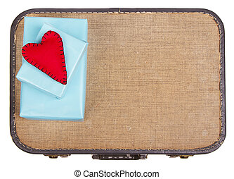 Handmade felt hearts sitting on presents on top of a suitcase