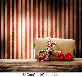 Handmade gift box with red twine cord over striped background