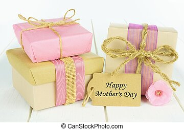 Handmade gift boxes with Happy Mother's Day tag on white wood