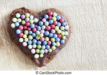 Handmade gingerbread heart decorated with colorful sugar pearls