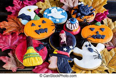Handmade halloween cookies with icing on autumnal foliage