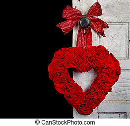 a red handmade heart made out of felt hangs on the door knob on a vintage door.