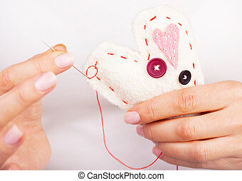 Photo of white handmade heart-shaped soft toy, Valentine day, romantic relationship, cardiology hospital, medical help, healthy lifestyle, beautiful present, love and health care concept