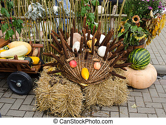 handmade hedgehog made from cat's-tails apple wicker basket courgette zucchini. autumn goodie decoration in outdoor fair market.