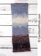 Handmade knitted scarf, wooden background.