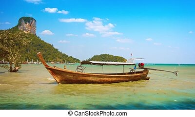 Handmade Longtail Boat Anchored near a Tropical Beach -...