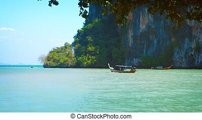 Video 2160p - Handmade, wooden longtail boat, cruising slowly along at the base of limestone seacliffs at a tropical island on a sunny day.
