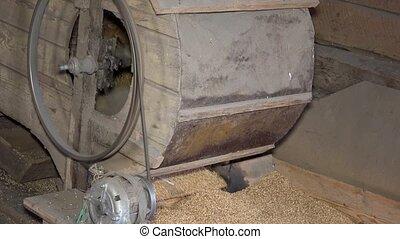 handmade machine sifting grain in barn. Closeup shot.