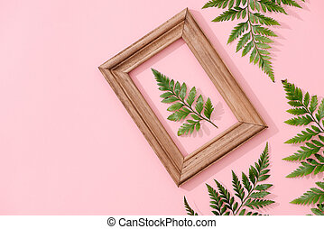 Handmade minimalist botanical interior decor, green tropical leaves in wooden frames hanging on pink background
