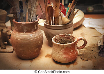 Handmade old clay pots with other stuff on the table