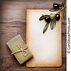 Handmade Olive Soap and Blank Paper with Olive Branch over Wooden Background
