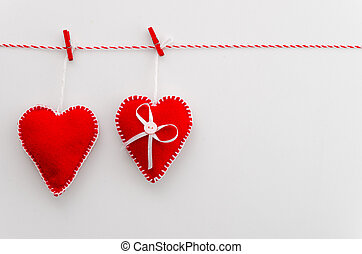 Handmade red hearts of felt on a rope with clothespin. Idea, decoration, invitations, flat lay top view, white background