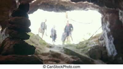 Handmade stone tower in cave in front of group of friends in...