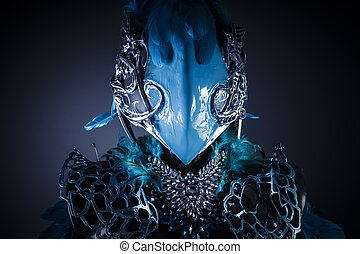 Handmade styling of a bird or mythological figure with blue wings and pieces of metal and precious stones