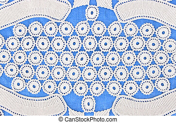 Handmade white lace on blue background