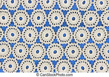 Handmade white lace on blue background