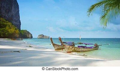 Handmade Wooden Tourist Boats Moored along a Sandy, Tropical...