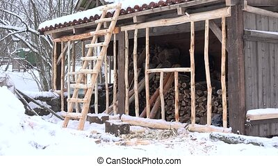 woodshed with firewood pile and ladder at snowy winter time....