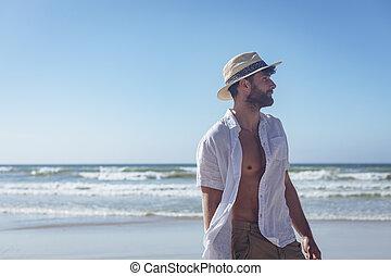 Handosme man standing at beach