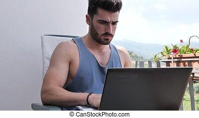 Handosme Man Working at Home at Computer Desk - Waist Up...