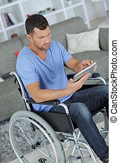 handosome man on wheelchair typing on his tablet at home