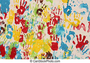 Handprints in different colors in a mural. Background...