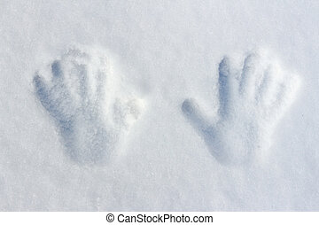 Handprints of a child on white fluffy snow as a background