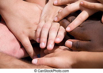 A diverse pile of hands signifying togetherness.