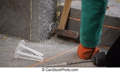 Hands affixing polystyrene panel on foundation - Worker...