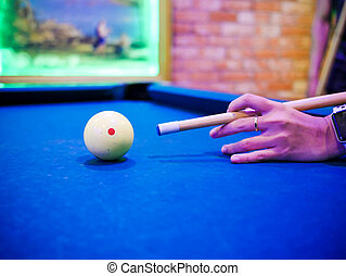 Hands aiming white ball to shot close up