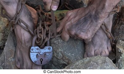 Hands and feet of a slave entangled in iron chains. An attempt to break free from slavery. The symbol of slave labor. Hands in chains