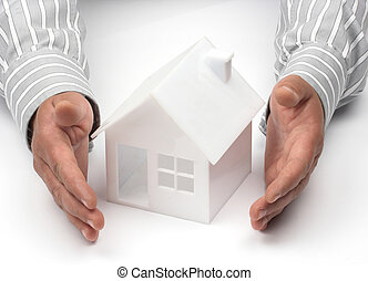 Real property or insurance concept - Hands and house model. ...