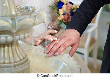 Hands and rings of the bride groom on a water fountain.