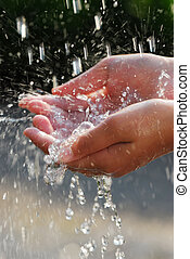 Hands and water - Hands catching clean falling water close...