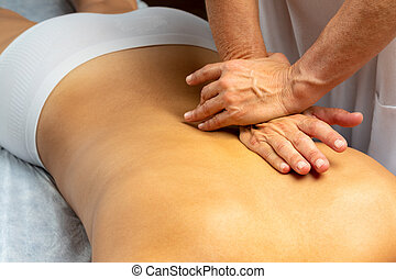Hands applying pressure along spine on female patient.