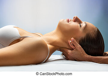 Hands applying pressure on back of woman's head.