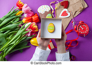 hands are holding a gift box with Easter eggs
