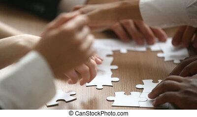 Hands assembling jigsaw puzzle, help support in teamwork concept, closeup