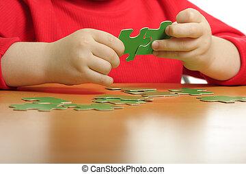 Hands assembling puzzle - Boys hands assembling green...